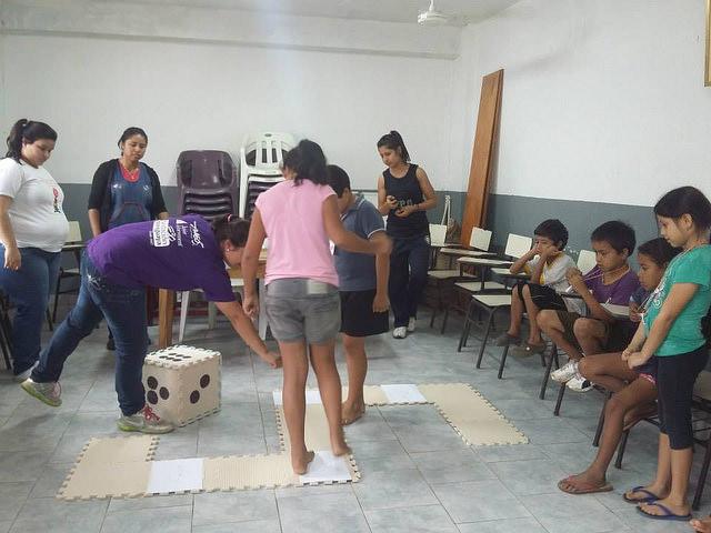Niñas y niños jugando con el dado Foto: Camila Cubilla, ONG Kuñamba J.A